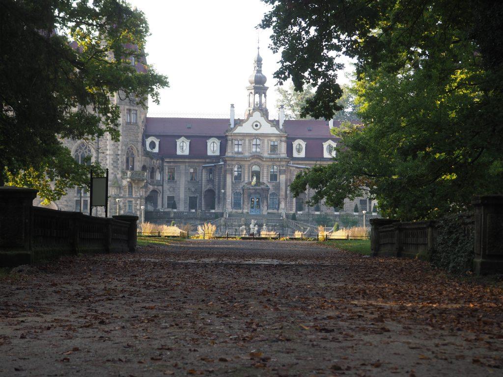 Przy pałacowy park, a w oddali barokowa część Pałacu w Mosznej