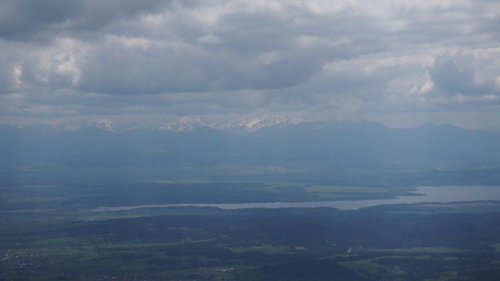 Widok na Jezioro Orawskie i będące zza chmurami Tatry